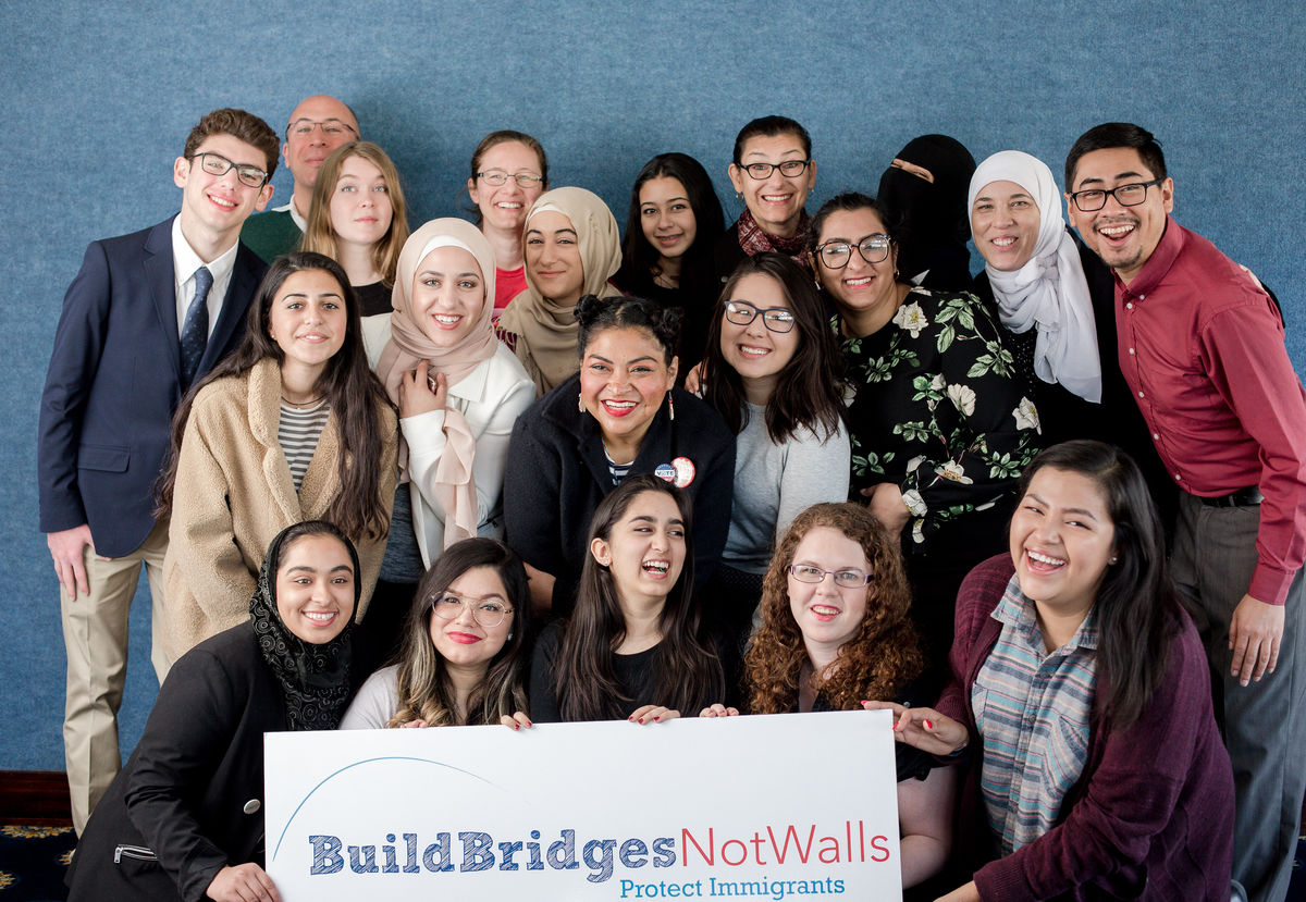 """Spring Lobby Weekend participants holding sign that says """"build bridges, not walls"""""""