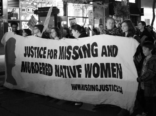 """Marchers carrying a sign that says """"Justice for Missing and Murdered Native Women"""""""