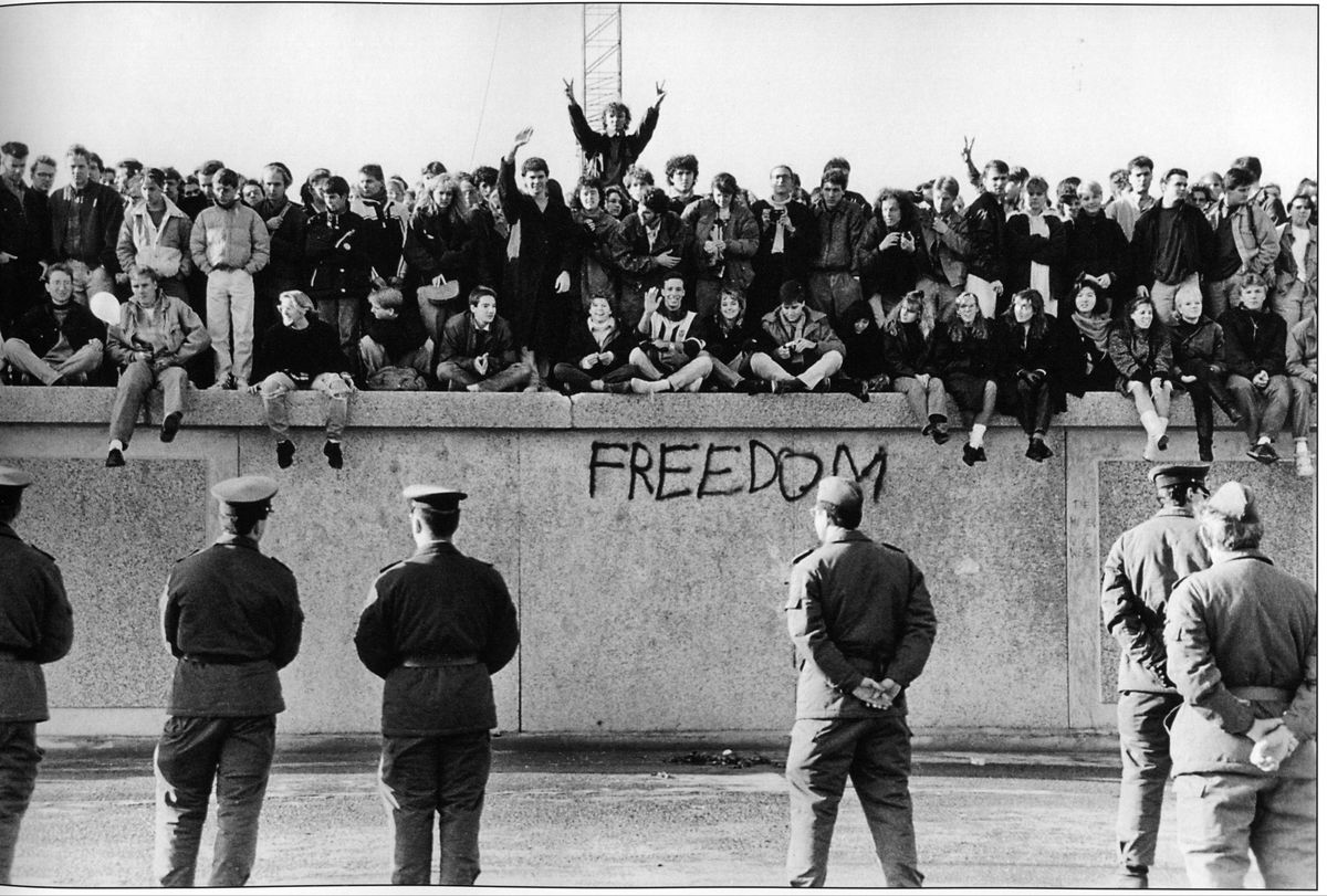 East German students sit atop the Berlin Wall, November 1989.