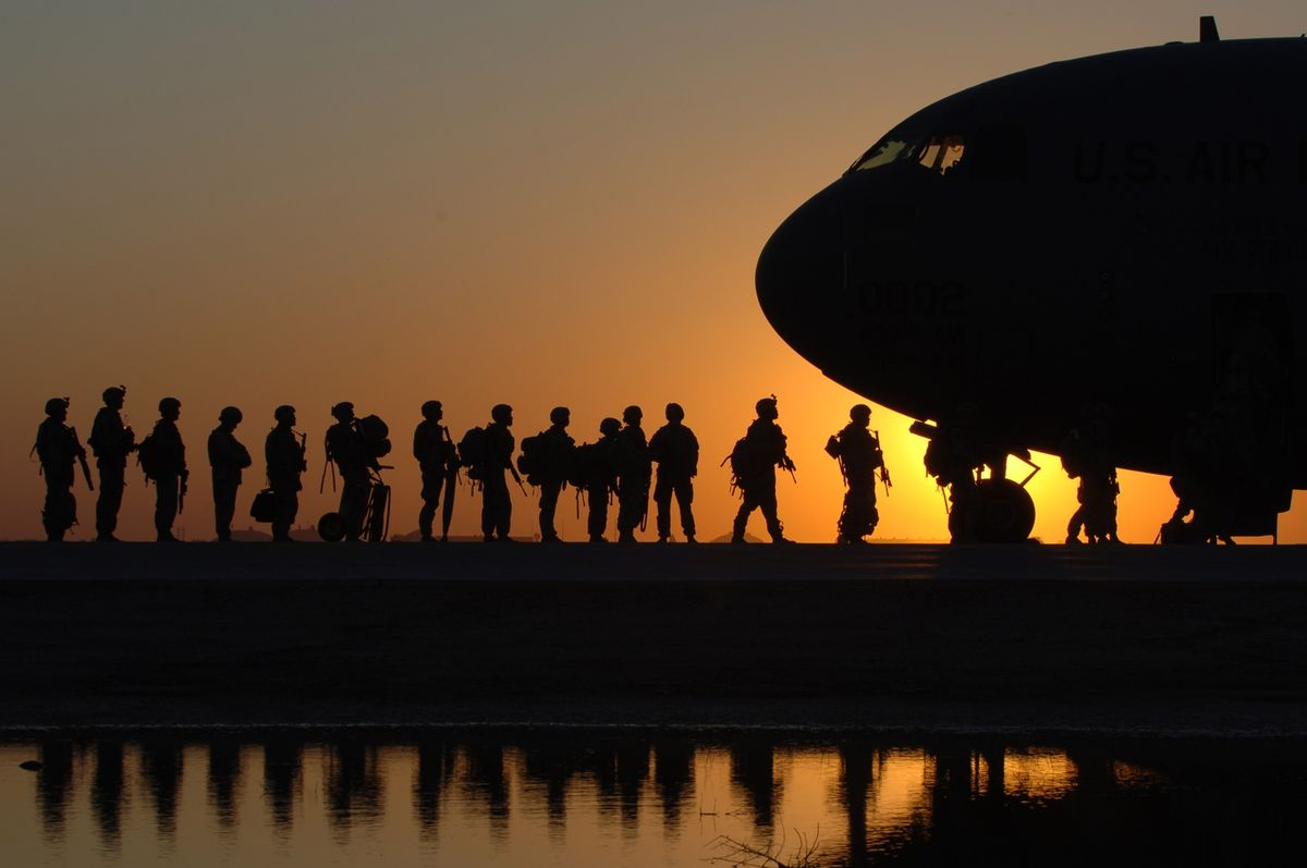 Soldiers boarding plane at sunset.