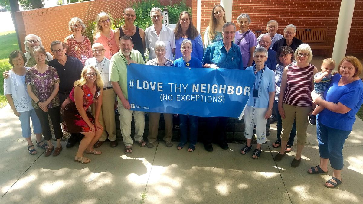 Christine Ashley with Friends holding Love They Neighbor banner