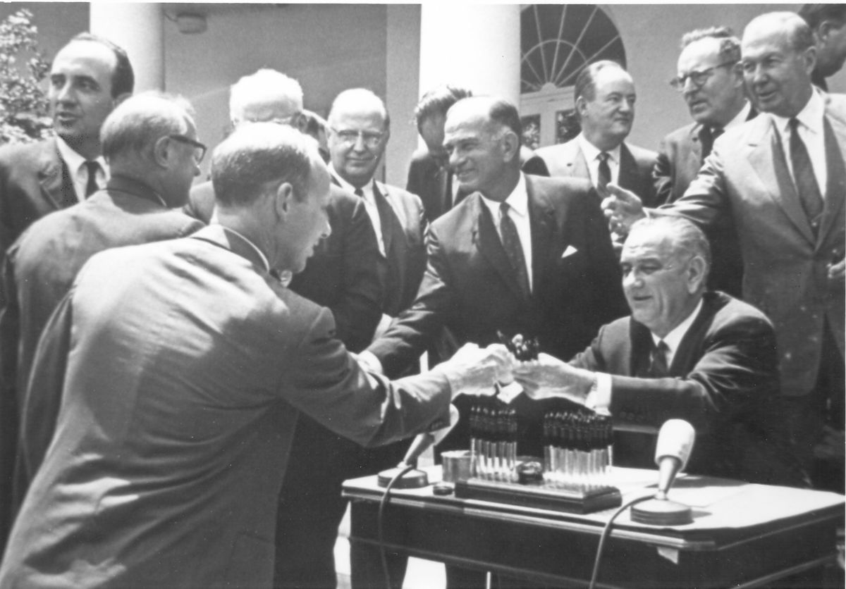Ed Snyder receives a pen from Pres. Lyndon B. Johnson after signing the 1965 Arms Control & Disarmament Act Extension.