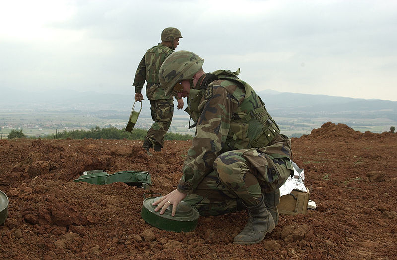 Soldiers laying down landmines.