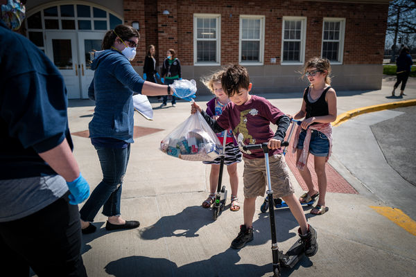 Des Moines Public Schools launched a huge increase in the number of free meal sites for students during the COVID-19 closure, going from 22 to 50 locations around the city. Here students on scooters receive a bag of food from volunteers.