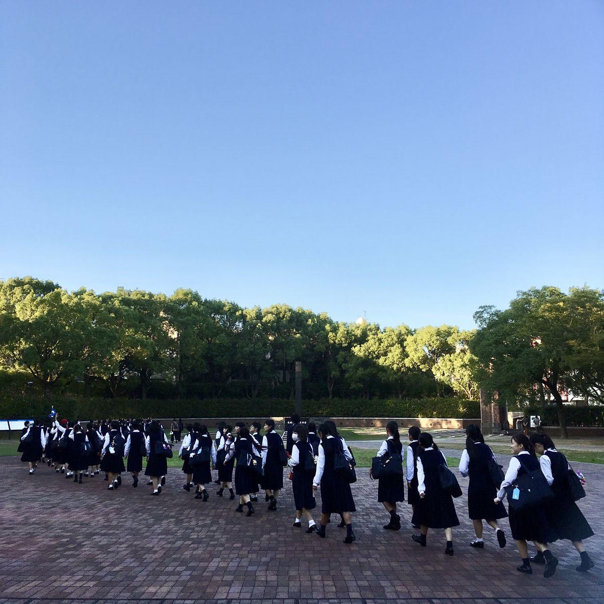 School children walk by the Nagasaki hypocenter cenotaph.