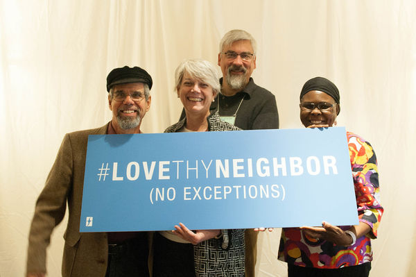 Group holds a love thy neighbor sign