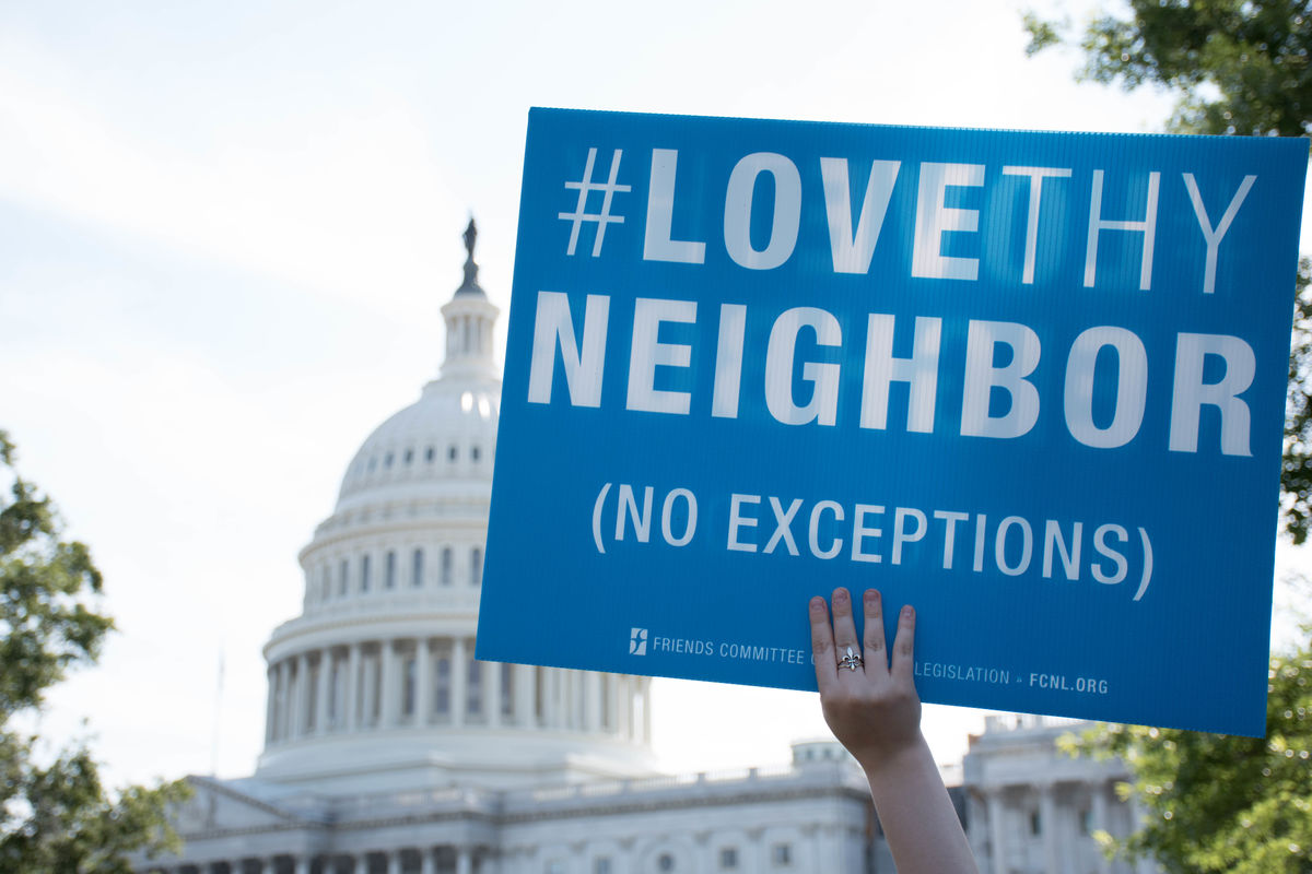 A Love Thy Neighbor sign with the Capitol in the backdrop.