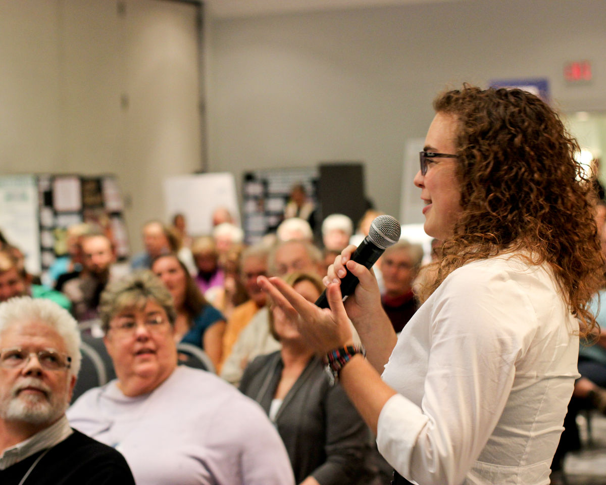Young person speaking in front of crowd