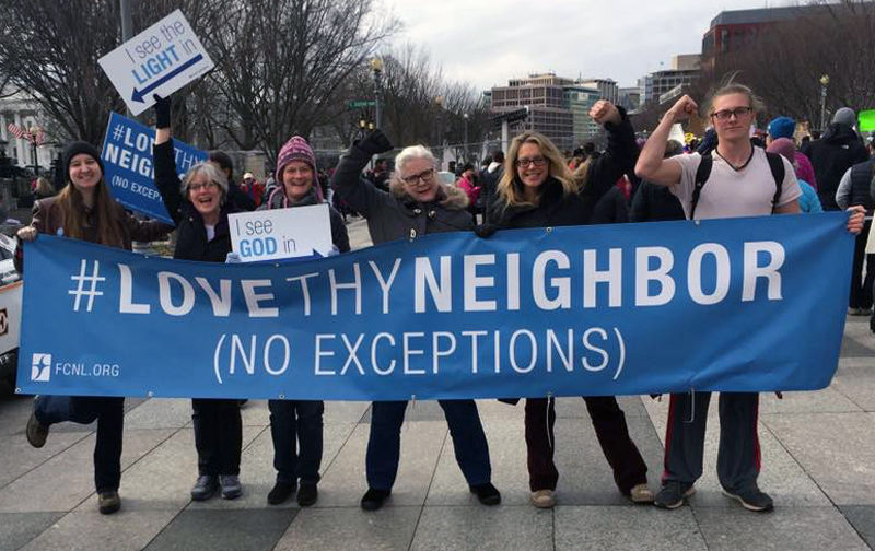 People holding Love They Neighbor Banner at a march.