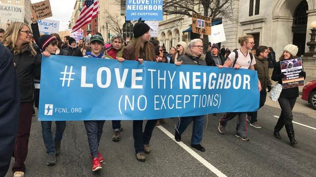 Christine Ashley and kids marching with Love Thy Neighbor Banner