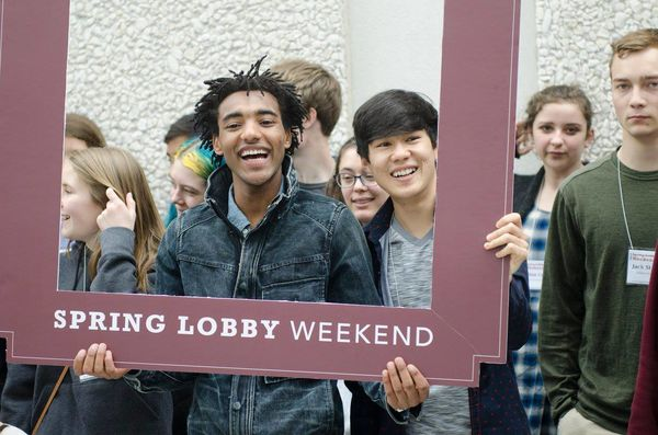 Students hold Spring Lobby Weekend sign